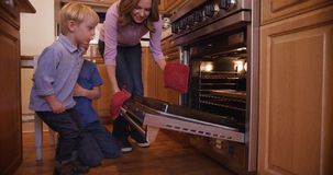 Lovely mother opens baking oven door for cookies Royalty Free Stock Images