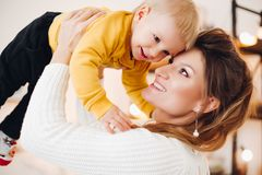 Lovely mother rising up her baby and smiling to each other. royalty free stock photo