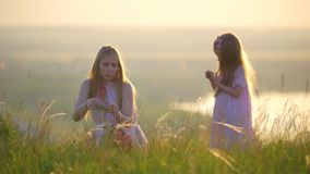 Lovely mother weaves a wreath with herbs for little daughter on the hill at sunset stock video