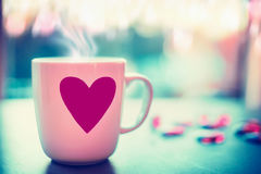 Lovely mug with pink heart on window sill at evening nature background with bokeh, front view. Love symbol or Valentines day Stock Photography