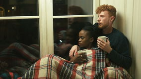Lovely multi-race couple lying under the red plaid on the window-sill. The man with red hair and beard is drinking tea