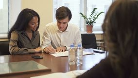 Lovely multiethnic couple in real estate agency office signing mortgage contract. African woman and caucasian man buying stock footage