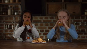 Relaxed diverse kids drinking juice in the kitchen. Lovely multiracial little girls eating cookies and drinking fresh juice while sitting at kitchen table during stock footage