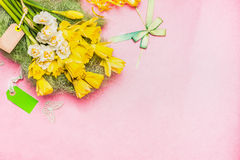 Lovely Narcissus bunch with blank tag and ribbon on pastel pink background, top view, place for text Royalty Free Stock Photo