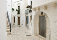 Lovely narrow street in the village of Locorotondo, southern Italy. Pictured is a lovely narrow street in the village of Locorotondo.  It is decorated with Royalty Free Stock Photos