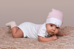 Lovely newborn girl creeps on bed, dressed in beautiful pink hat, looks innocently into camera. Small baby ejoys time with parents. Little cute daughter in Royalty Free Stock Image