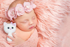 Lovely newborn girl holding toy on pink fluffy blanket Stock Photos