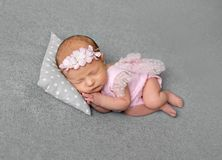 Lovely newborn girl in pink drees sleeping. Lovely newborn girl in pink dress sleeping with pillow under her little head. Little princess with flowery hair band Royalty Free Stock Images