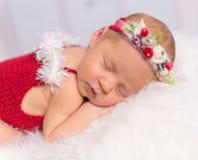 Lovely newborn girl in red romper sleeping on fluffy blanket Royalty Free Stock Photos