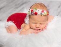 Lovely newborn girl in red romper sleeping on fluffy blanket Royalty Free Stock Photography