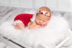 Lovely newborn girl in red romper sleeping on fluffy blanket Stock Image