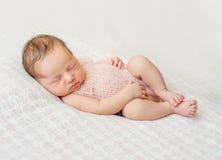 Lovely newborn girl sleeping on pink blanket. With bare feet Stock Photo