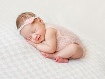 Lovely newborn girl sleeping on pink blanket. With bare feet Stock Image