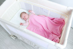 Lovely newborn girl sleeps in travel crib. Newborn girl sleeps in travel crib Stock Photography