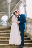 Lovely newlywed pair - groom holding his pretty bride while both stand on antique stone stairs. Full length portrait.  Royalty Free Stock Images