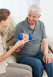 Lovely nurse helping her patient to do exercises stock photo