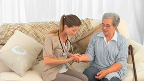 Lovely nurse taking the pulse of her patient at home Royalty Free Stock Images