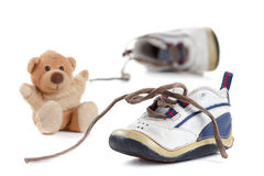 Lovely old Baby's shoes with a teddy bear Royalty Free Stock Image