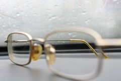 Lovely old glasses against glass with drops Stock Images