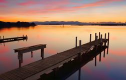 Lovely old timber jetty at sunrise. Rustic old timber jetty with old basin on calm waters at sunrise Stock Photo