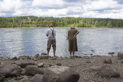 Lovely older couple standing beside the lake fishing Stock Images