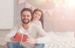 Lovely optimistic family ready for mothers day. Emotional waiting. Two cute charming vibrant people holding a present ready and sitting on the couch after stock image