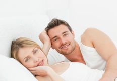 Lovely pairs lying down together in their bed. At home Royalty Free Stock Image