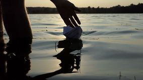 Lovely paper boat is launched by a boy in a lake at sunset in slo-mo. A white paper boat is launched bya teenager boy in a forest lake at a splendid sunset with stock video