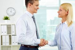 Lovely partner. Handsome businessman shaking the hand of his lovely business partner Stock Image