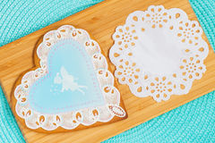 Lovely pastel blue gingerbread shaped openwork heart with image of cute little girl's fairy and tracery paper napkin Royalty Free Stock Photography