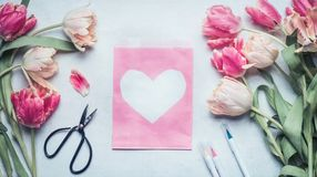 Lovely pastel color spring mock up with tulips, scissors , markers and pink pack paper bag  with heart. Top view, flat lay Royalty Free Stock Images