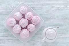 Lovely pastel rose meringues, zephyrs, marshmallows and a coffee pot on the wooden vintage table Royalty Free Stock Image