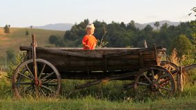 Lovely peasant child with a traditional cap, sit in traditional wooden cart. Full HD stock footage