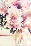 Lovely peonies bunch in glass vase on table with bokeh lighting. Romantic flowers bouquet, front view Stock Photography