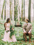 The lovely photo of the newlyweds looking at each other while sitting on the chairs between the hanging stump with the. Wedding sponge green and white cake on Royalty Free Stock Photography