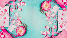 Lovely pink flowers with petals and pink paper shopping bags on light blue background, top view, banner. Royalty Free Stock Photo