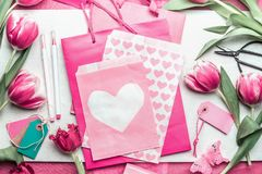 Lovely pink mock up with tulips, paper package with hearts, marker pen, tags and scissors on creative desktop, top view, frame. Layout of spring greeting card Royalty Free Stock Images