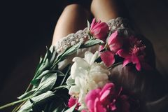 Lovely pink peonies on legs of boho girl in white bohemian dress stock photography