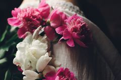 Lovely pink peonies on legs of boho girl in white bohemian dress, top view. space for text. stylish hipster woman sitting with. Beautiful flowers in morning royalty free stock photo