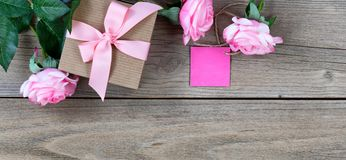 Lovely pink roses plus gift box with tag for Mothers Day holiday Royalty Free Stock Photo