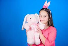 Lovely playful bunny child hugs soft toy. Bunny ears accessory. Bunny girl with cute toy on blue background. Child. Smiling play bunny toy. Have blessed Easter royalty free stock photo