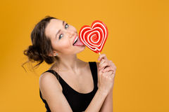 Lovely playful woman licking sweet heart shaped lollipop Stock Images