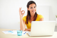 Lovely pleased secretary working at her office. Lovely pleased secretary in a business company working at her office while is showing you a positive feedback Royalty Free Stock Images