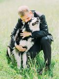 The lovely portrait of the groom hugging the dog in the park. The lovely portrait of the groom hugging the dog in the park Stock Photos