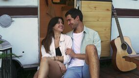 Lovely portrait of a young couple. They are sitting on the stairs of their modern trailer, embracing and smiling