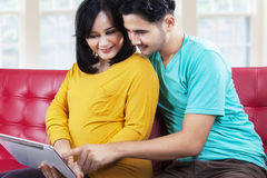 Lovely pregnant couple with tablet on sofa Stock Photos