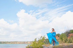 Lovely pregnant girl against a background of water and sky in a cloth. royalty free stock image