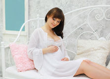 Lovely pregnant woman on the bed Stock Image