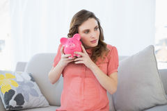 Lovely pregnant woman shaking a piggy bank sitting on couch Stock Photo
