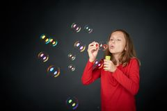 Girl blowing soap bubbles stock image